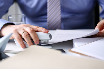 Male clerk arm pin together some papers with stapler