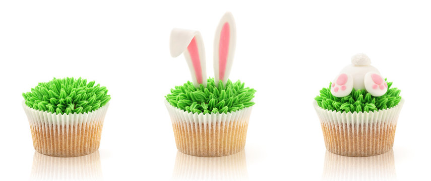 Easter cupcakes isolated on white. Grass, bunny butt and ears.
