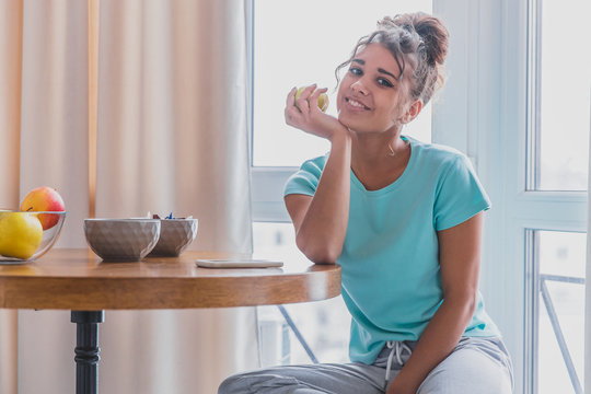 Beautiful, calm young woman with a cup of coffee, relaxing hot drink, happy lady holding a cup. Pretty brunette. The girl is sleepy. Food and drink.