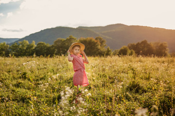Cute blonde girl in straw hat and pink dress in the summer field at sunset