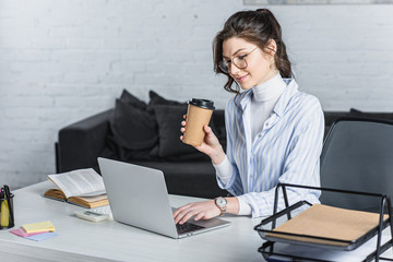 Attractive businesswoman holding paper cup and looking at laptop screen at office