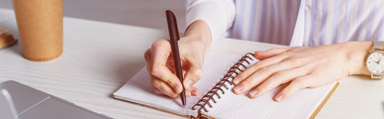 Cropped view of woman writing in notebook