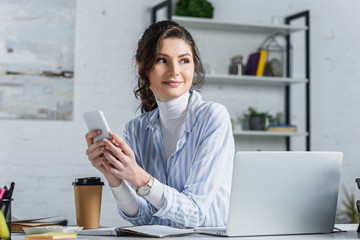 Attractive businesswoman holding smartphone and  looking away at office