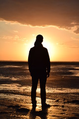 silhouette of man on the beach at sunset