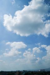 white cloud on clear blue sky above the city skyline