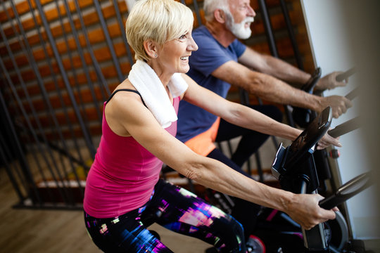 Mature fit people biking in the gym, exercising legs doing cardio workout cycling bikes