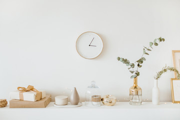 Modern interior design concept. Bright beige and golden apartment with clock, eucalyptus branch, vase, candle.
