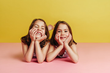Twin girls lying on pink floor