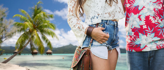 summer, fashion and people concept - close up of young hippie couple over tropical beach background in french polynesia