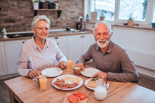 Portrait of a senior couple sitting at table having breakfast at home, looking at camera.