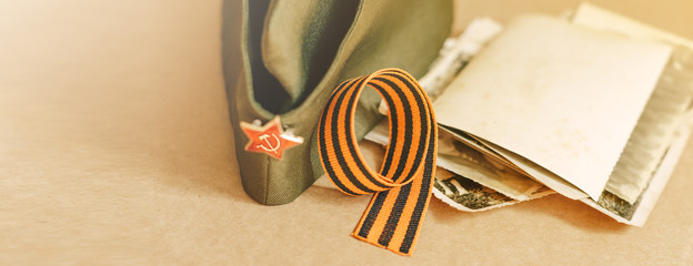 St. George ribbon on a paper background / St. George ribbon-a symbol of the great Victory/Victory Day. The child's hands and the veteran. Concept of memory after the war.