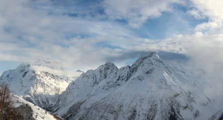 snowy mountain peaks in winter day with blue sky in Dombay, Caucasus, Karachay-Cherkessia, Russia