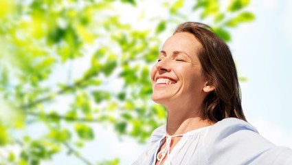 people and leisure concept - happy smiling woman enjoying sun over green natural background