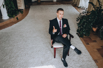 Stylish groom in a black suit is sitting on a chair in the room and smiling. Wedding photo. Beautiful portrait.