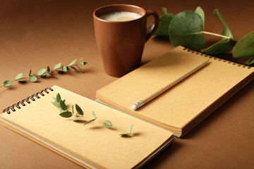 Notebooks, pencil and cup of coffee on color background