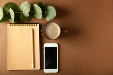 Notebook, mobile phone and cup of coffee on color background