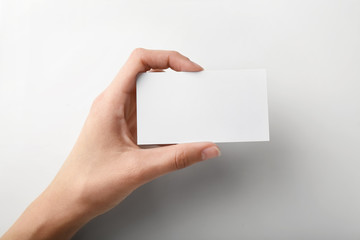 Female hand with blank business card on light background