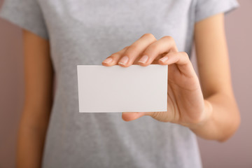 Young woman with blank business card, closeup