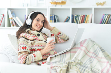 Portrait of young woman using laptop at home