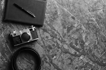 Stylish male accessories and photo camera on grunge background