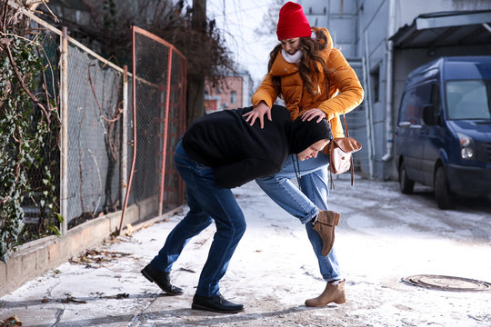 Young woman defending herself from thief outdoors