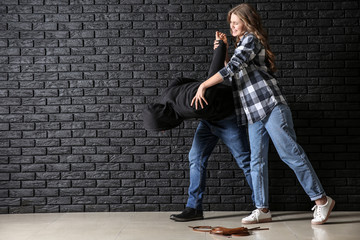Young woman defending herself from attack by thief near dark brick wall