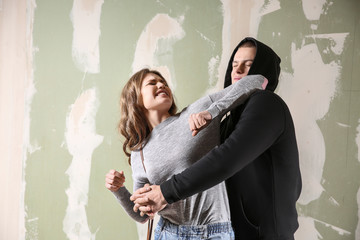 Young woman defending herself from attack by thief on color background Wall mural