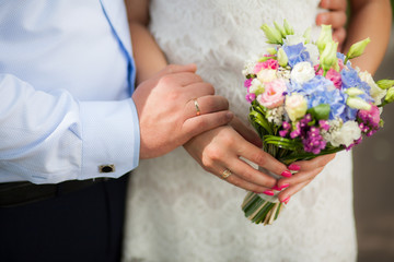 Closeup view of cute small colorful bridal wedding bouquet of flowers in hands of young beautiful bride. Horizontal color photography.