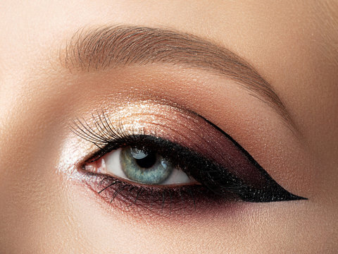 Close up of beautiful woman eye with multicolored fashion makeup and modern eyeliner wing. Studio shot