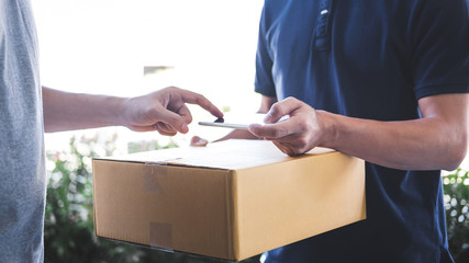 Delivery mail man giving parcel box to recipient, Young man appending signing in digital mobile...