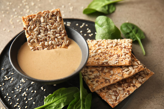 Bowl of tasty tahini with crackers on table