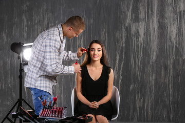 Professional makeup artist working with young model in photo studio