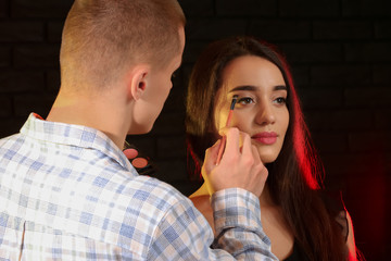 Professional makeup artist working with young model on dark background