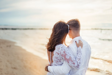 Happy young romantic cheerful loving wedding couple walking on the beach of sea. Happiness, couple, love concept