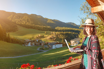 Happy successful young woman freelancer working remotely using a laptop in country cottage house with Alps mountains at the background