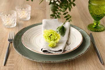 Beautiful festive table setting with floral decor on wooden background