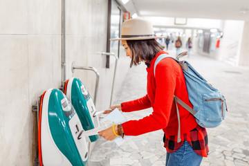 Woman validating ticket on modern public train transport