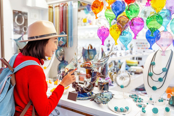 Woman tourist shopping for colorful decorated objects made of a famous murano glass in a shop window in Venice