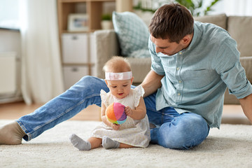 family, fatherhood and people concept - happy father and little baby daughter playing with ball at home