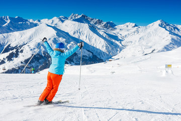 Back view of skier woman enjoys the winter ski resort.