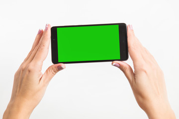 Close up mockup image of woman's two hands holding black mobile phone with blank green screen isolated on white background. Horizontal color photography.