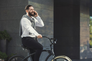 Businessman stop bicycle to talk on phone