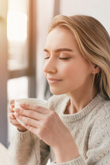 cheerful woman holding cup and smelling tea with closed eyes