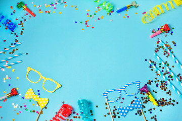 Holiday or party frame background with straws, whistles, confetti, funny glasses and streamer on blue background. Flat lay style.