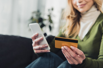 cropped view of woman holding smartphone and credit card in hands