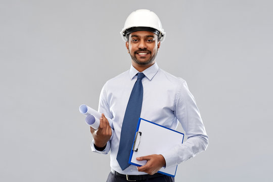 architecture, construction business and building - smiling indian architect or businessman in helmet with blueprints and clipboard over grey background