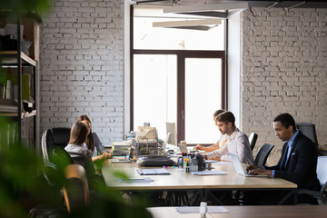 Diverse employees busy working in shared office