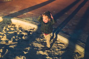 Little toddler in sandbox at sunset