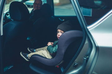 Little toddler sitting in his car seat