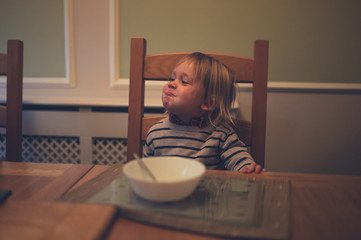 Little toddler eating from a bowl at a table